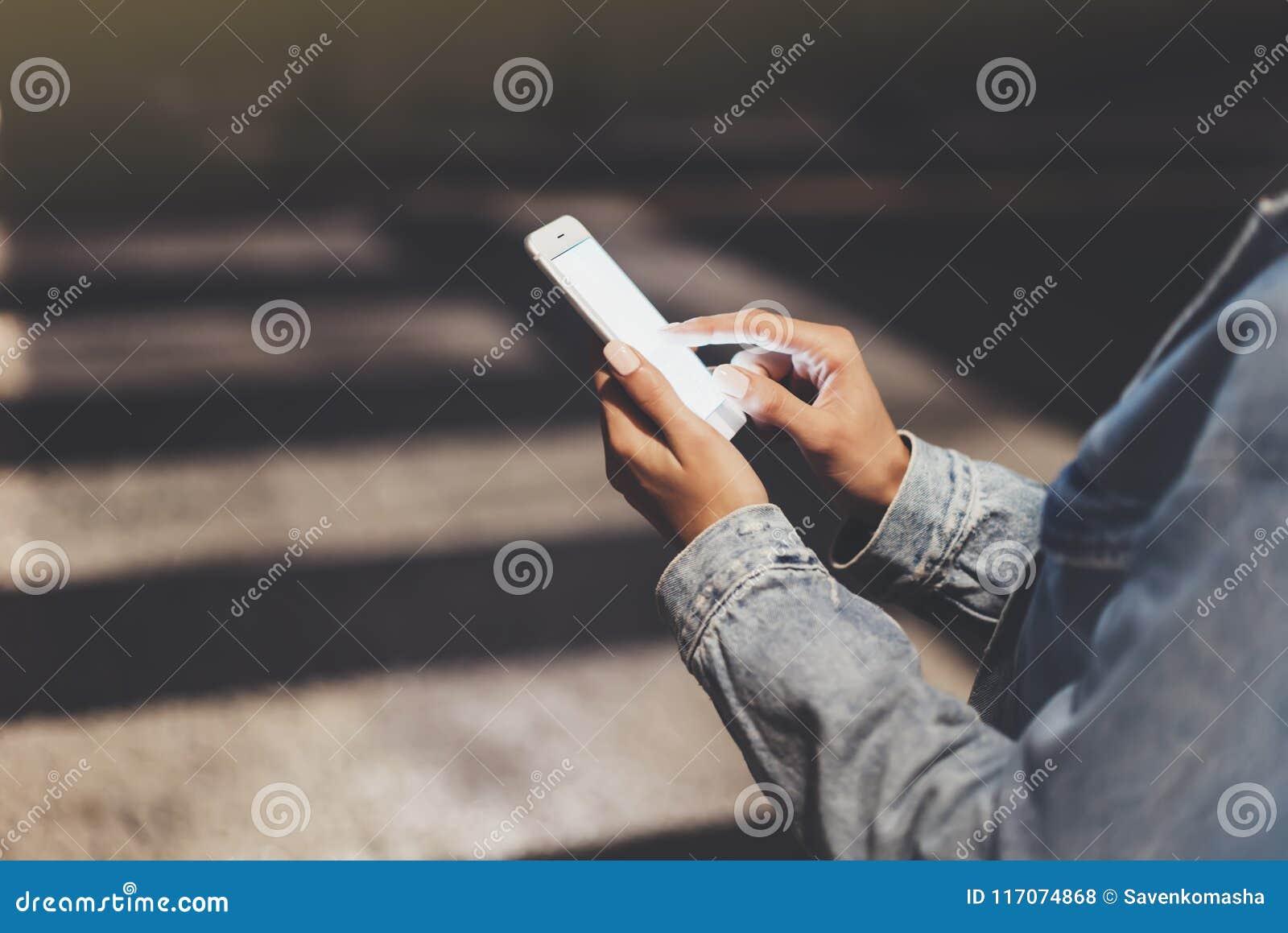 指向在屏幕智能手机的女孩手指在背景焕发bokeh光在夜大气圣诞节城市,行家使用