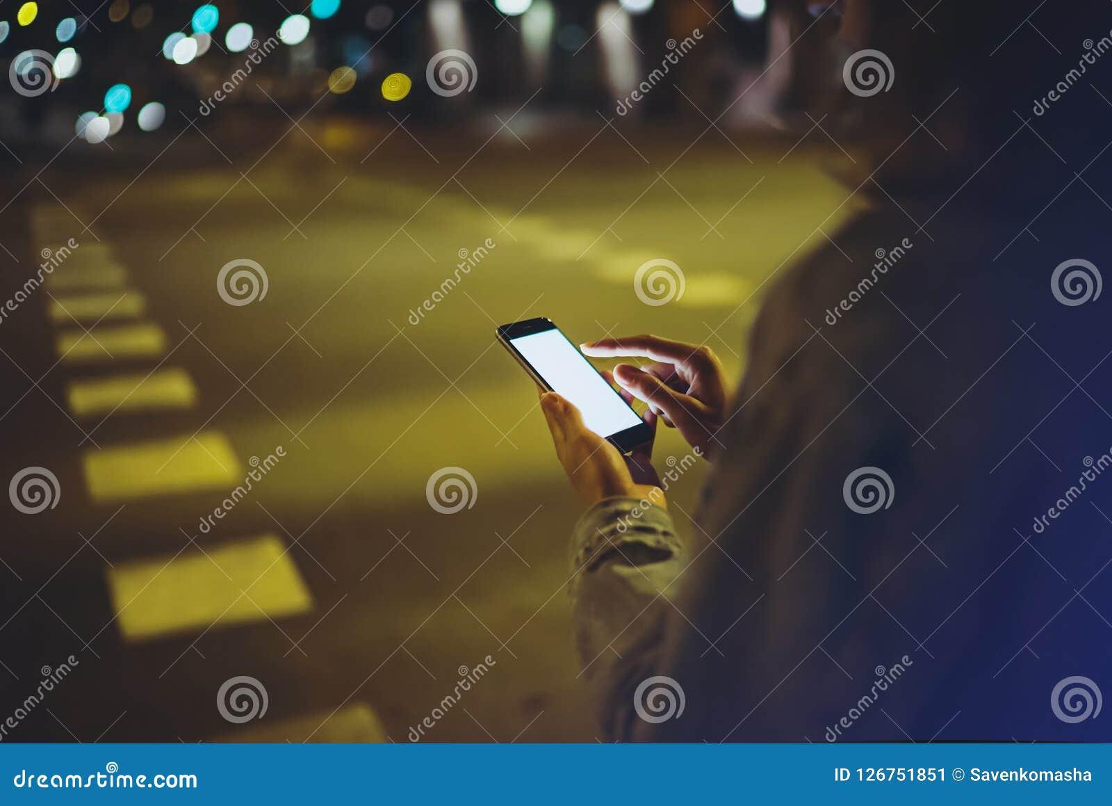 指向在屏幕智能手机的女孩手指在背景照明焕发bokeh光在夜大气城市,行家使用