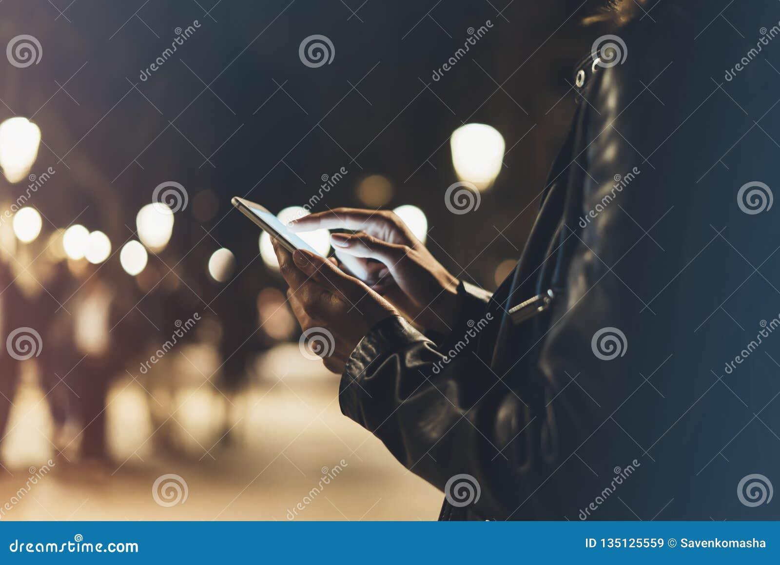 指向在屏幕智能手机的女孩手指在背景照明颜色光在夜大气城市,行家使用