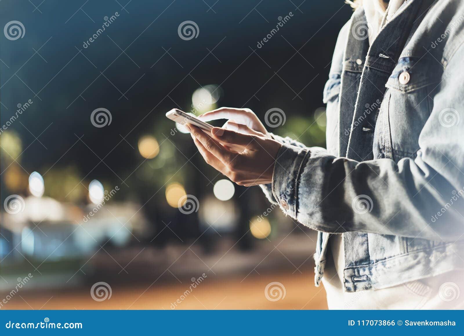 指向在屏幕智能手机的女孩手指在背景照明bokeh颜色光在夜大气城市,使用的行家