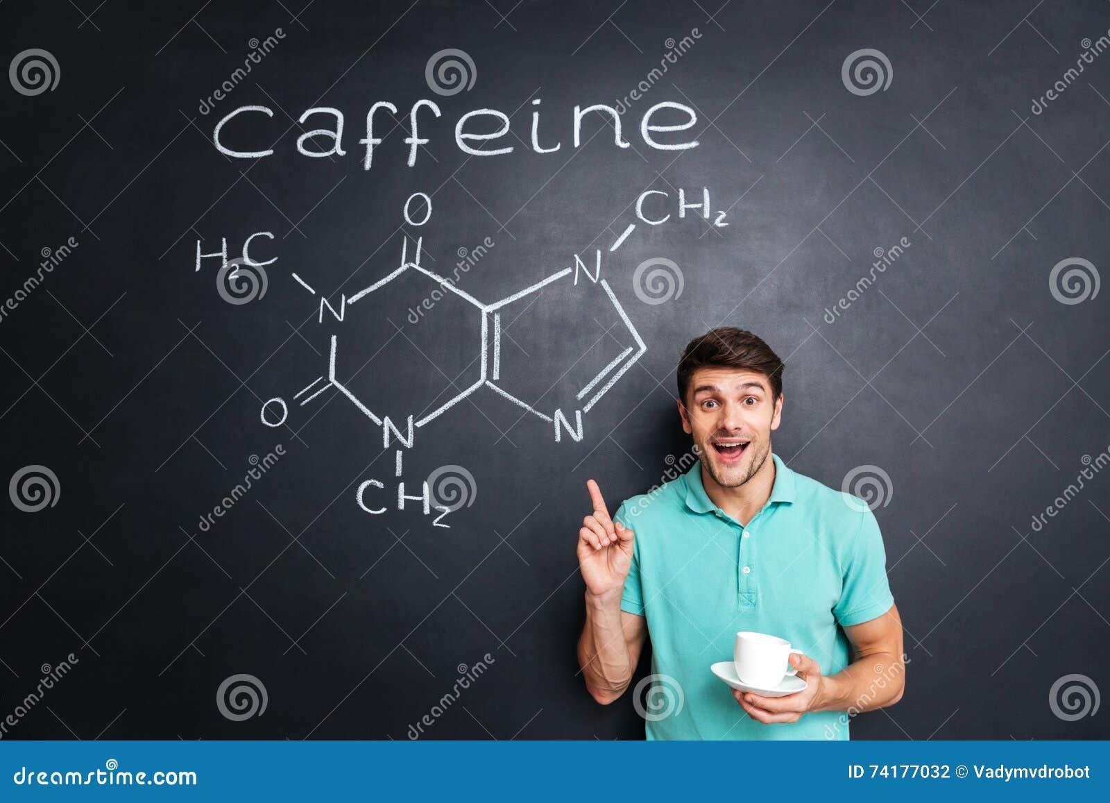 指向在拉长的咖啡因分子化学结构的微笑的年轻人