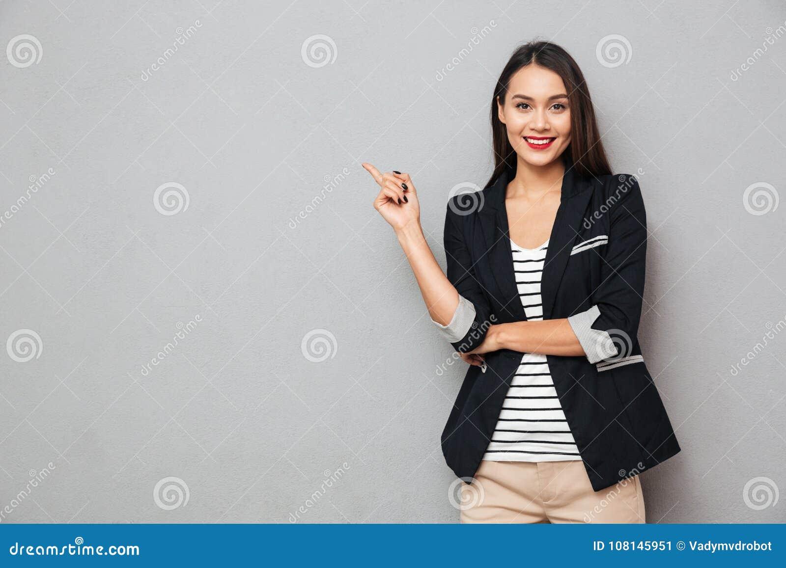 指向微笑的亚裔的女商人和看照相机
