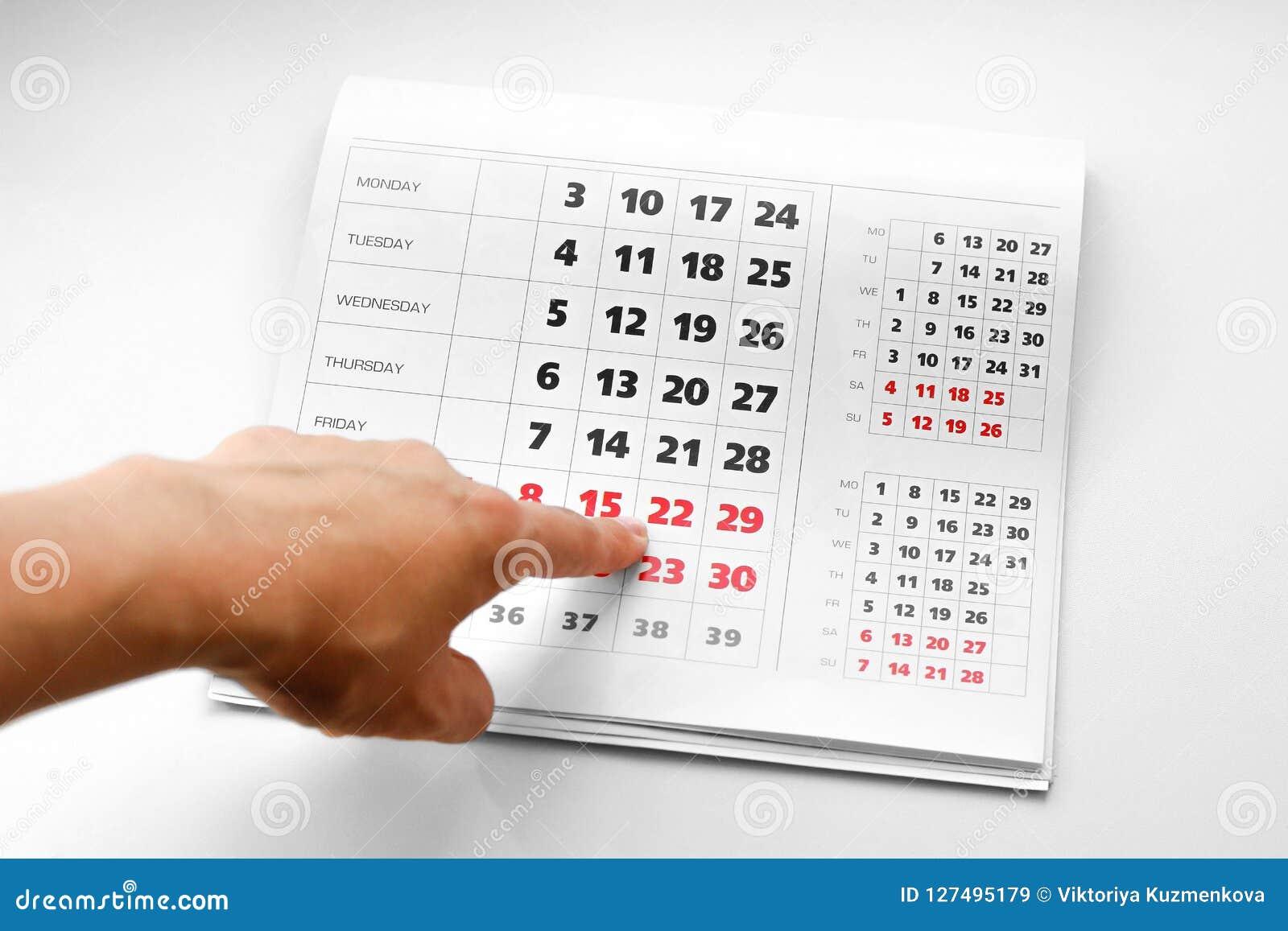 指向日历的手 白色日历 周末在红色被突出 关闭