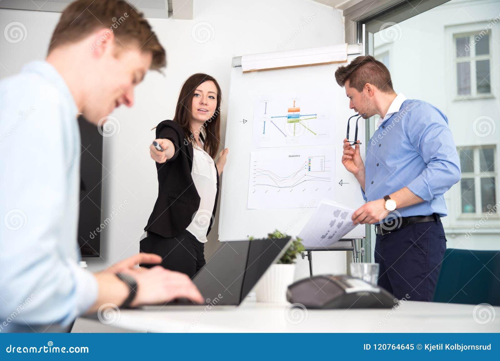 指向男性同事的女实业家使用膝上型计算机