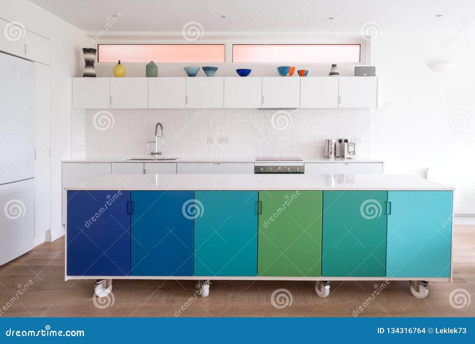 按客户需要设计的厨房在工业铸工轮子,在蓝色和绿色绘的减速火箭的设计的开放学制厨房里