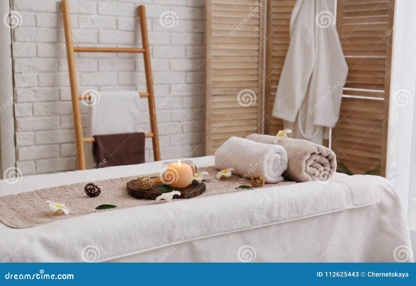 按摩与毛巾、蜡烛和海盐的桌在温泉沙龙