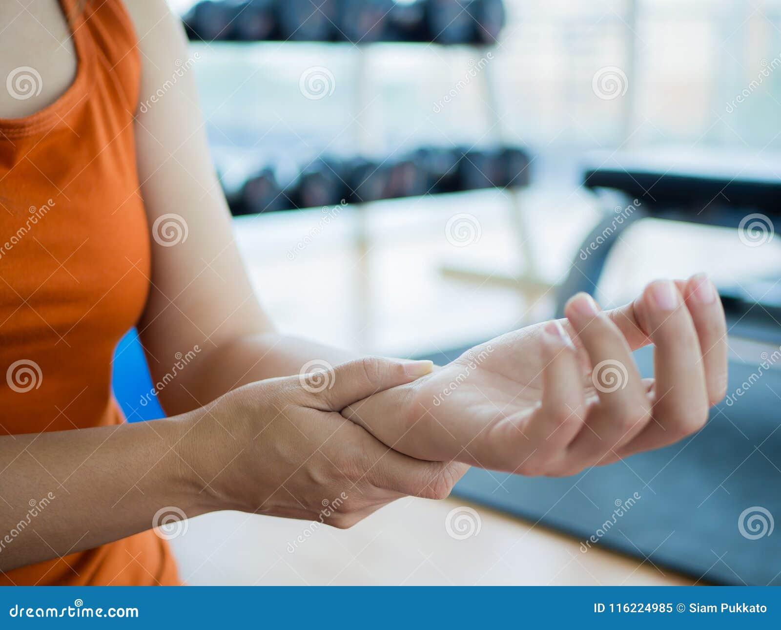 按摩她的腕子的少妇在解决以后