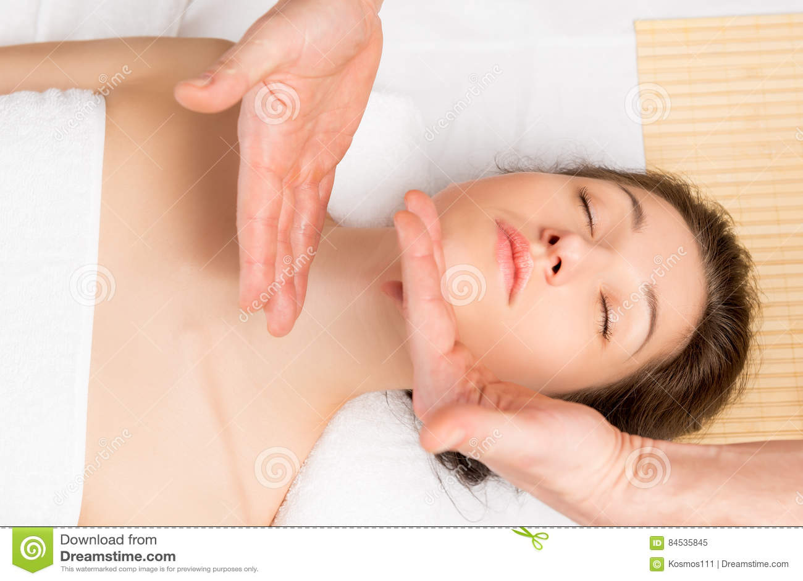 按摩脖子和面孔的手的美容师运动