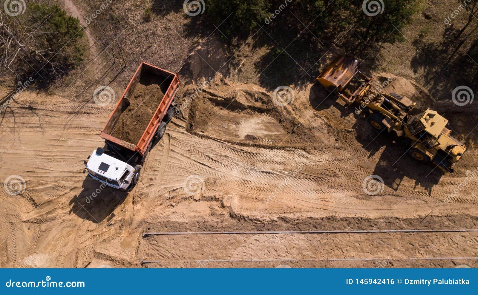 挖掘机装载的沙子到有航拍寄生虫的一辆卡车里