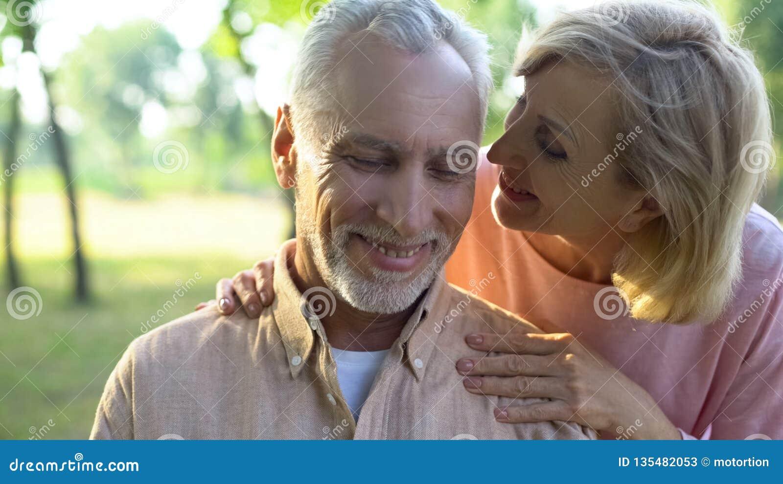 挥动与英俊的丈夫的关心的成熟妻子在公园,耳语的恭维