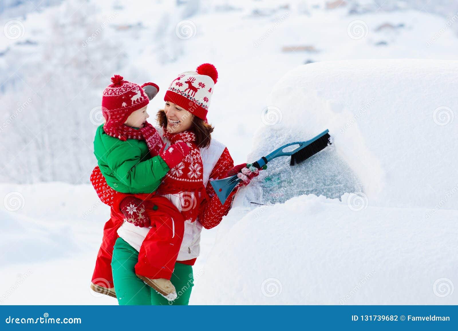 掠过和铲起雪的母亲和孩子汽车在风暴以后 父母和孩子与冬天刷子和刮板清洁家用汽车