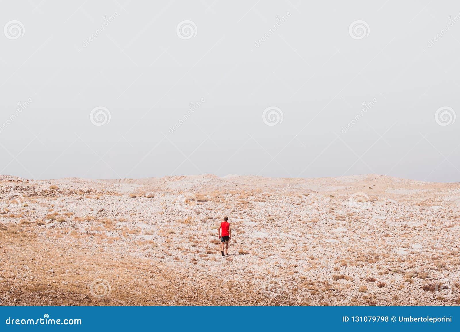 探索-偏僻人走在岩石沙漠自由和冒险生活方式和体育概念