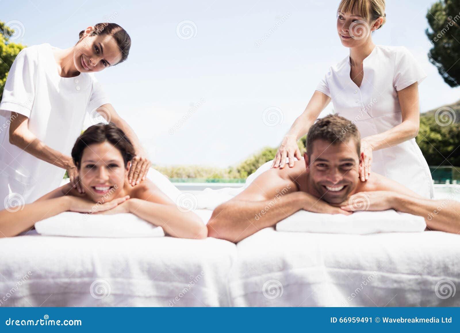 接受后面按摩的年轻夫妇从男按摩师