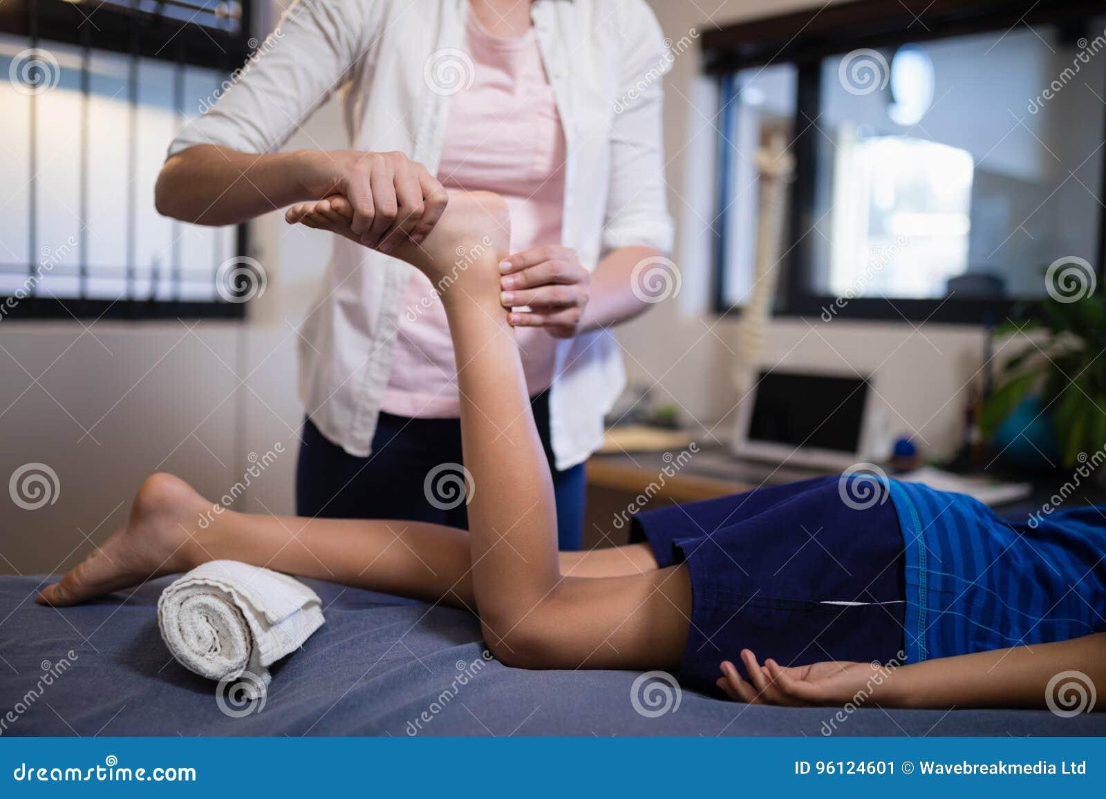 接受脚按摩的男孩的低部分从年轻女性治疗师