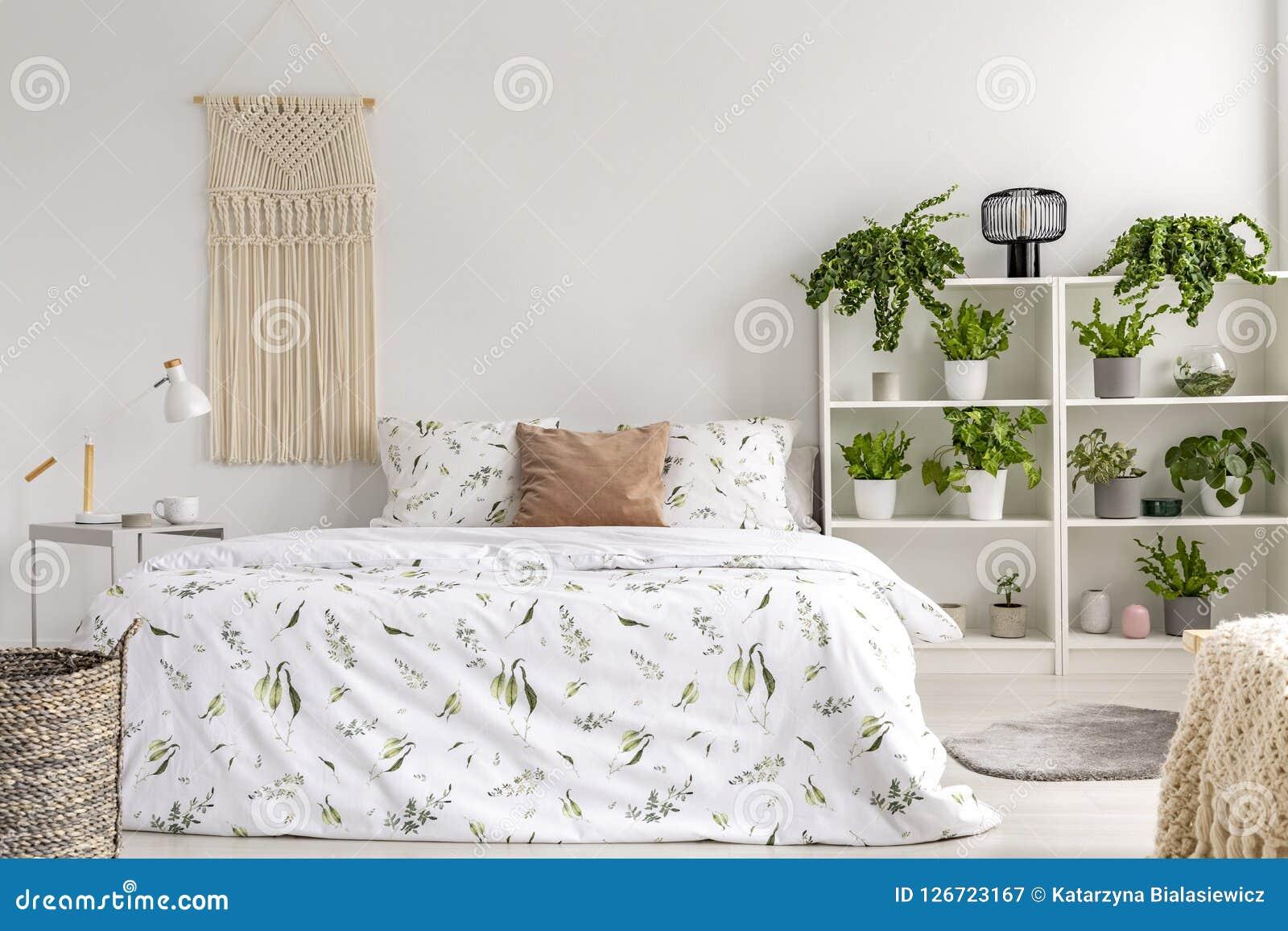 接近与许多绿色植物的自然明亮的卧室内部在一张大床旁边 在床上的被编织的挂毯 实际照片