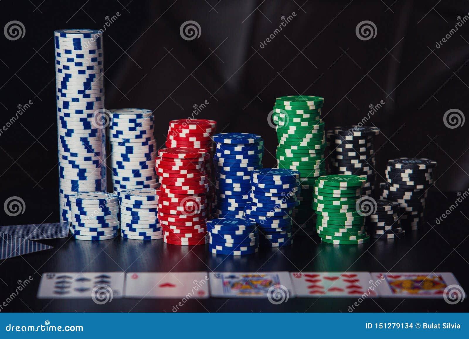 接近的堆不同的色的纸牌筹码和纸牌在赌博娱乐场桌上被隔绝在黑背景 ??