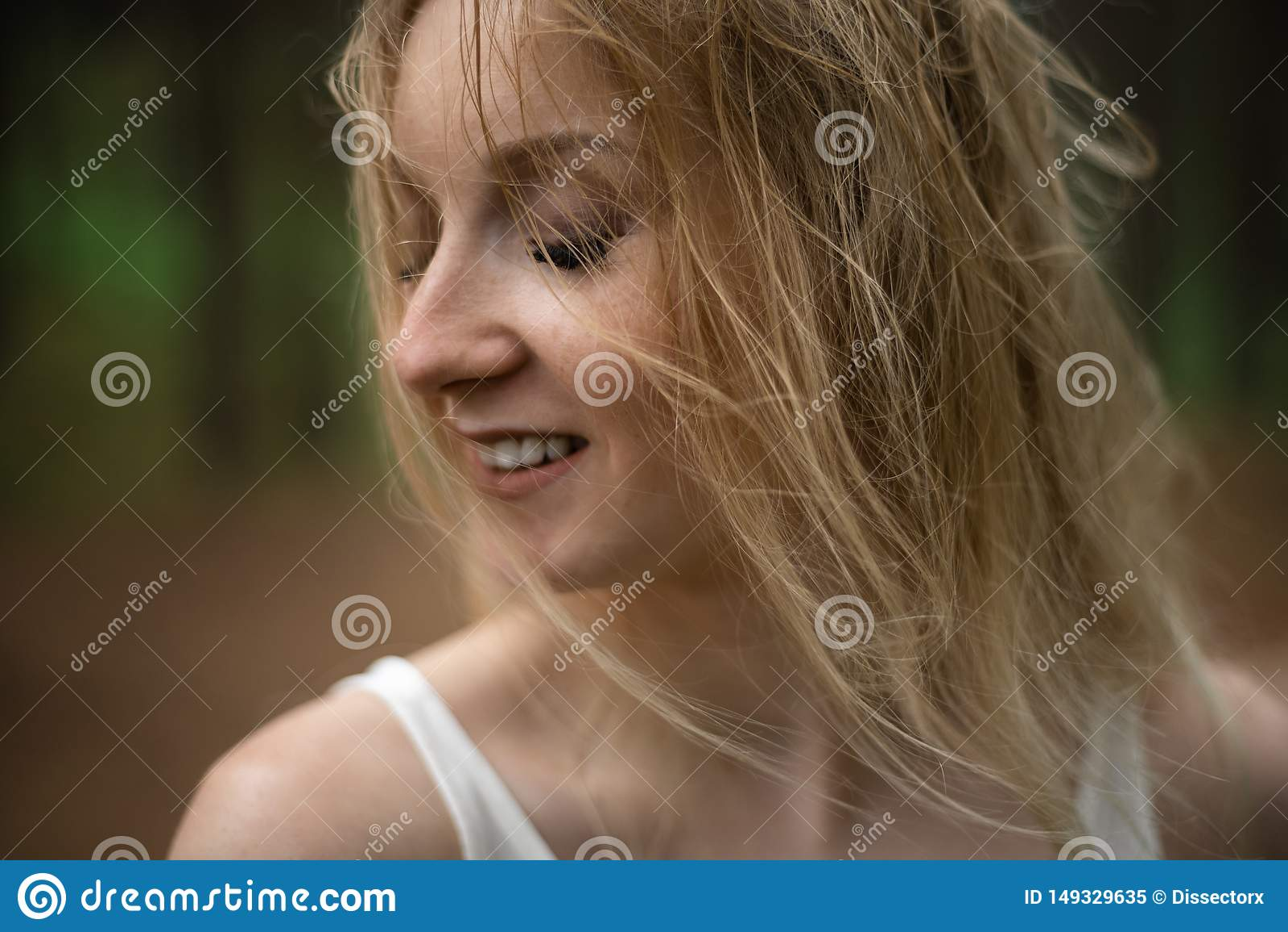 接近的画象-在白色礼服的美丽的幼小白肤金发的妇女森林若虫在常青木头