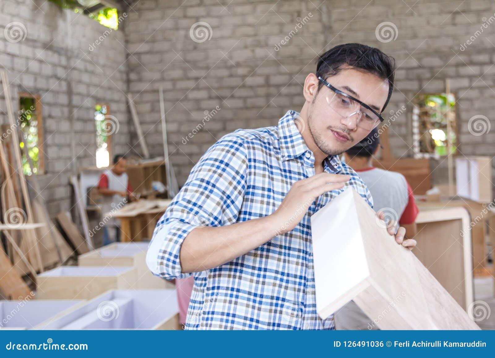 控制他的产品的年轻木匠质量