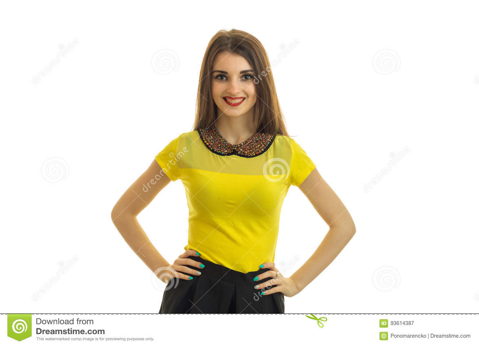 握在边和面孔的一个迷人的年轻微笑的女孩手在明亮的女衬衫的照相机