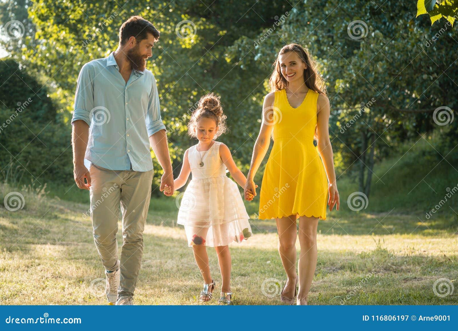 握女儿的手的充满爱心的父母,当一起时走