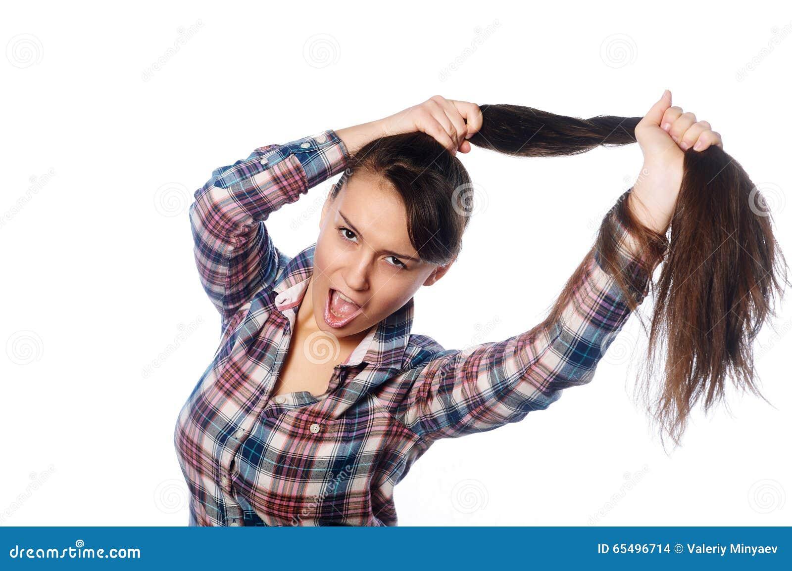 握她在马尾辫的可笑的快乐的女孩长的头发在白色背景