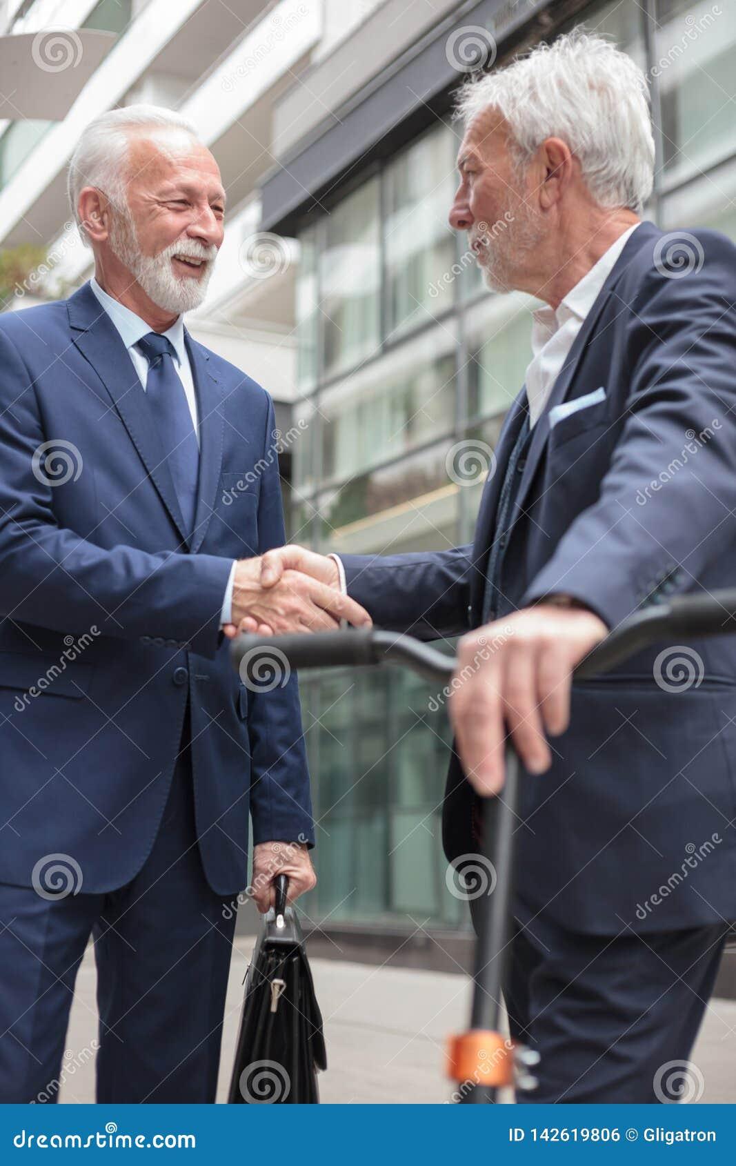 握手的两个愉快的资深商人,站立在办公楼前面