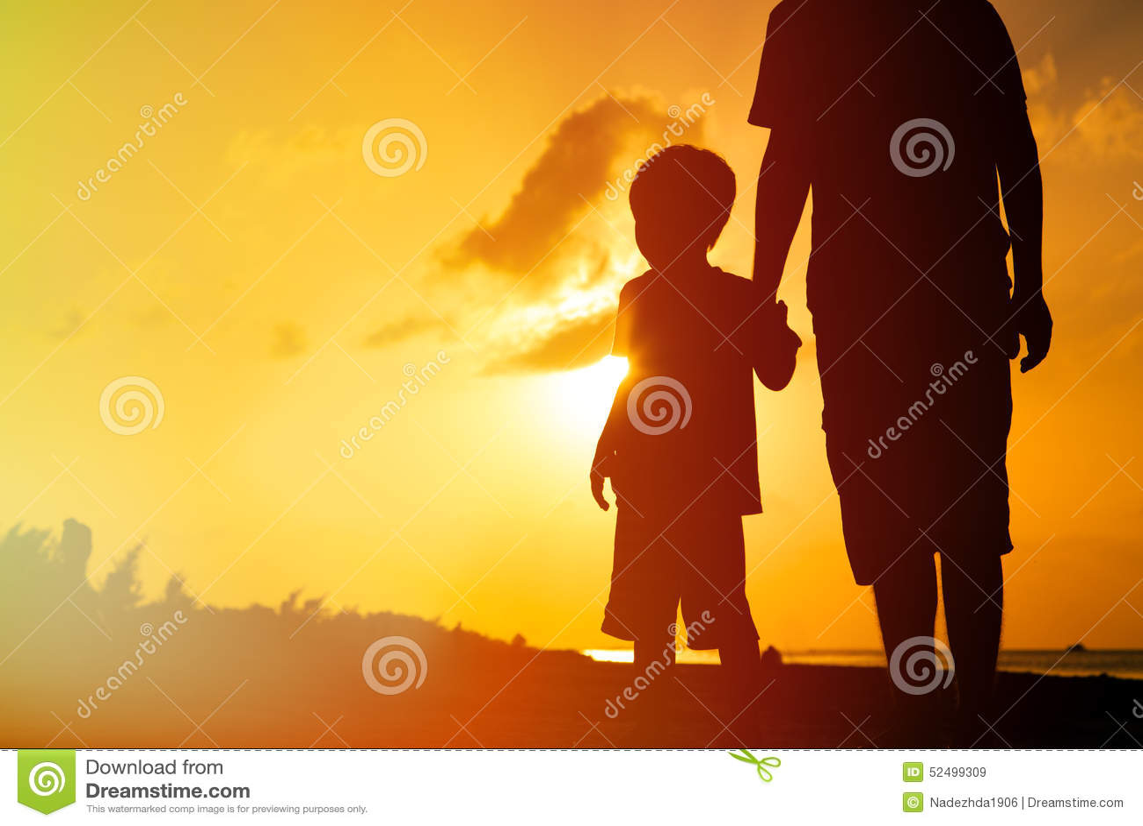 握手的父亲和儿子在日落海