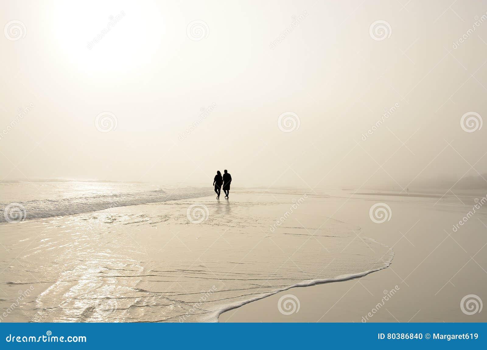握手的资深夫妇走在享受日出的海滩