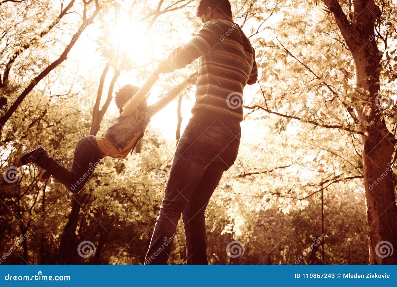 握父亲和r的手的非裔美国人的小女孩