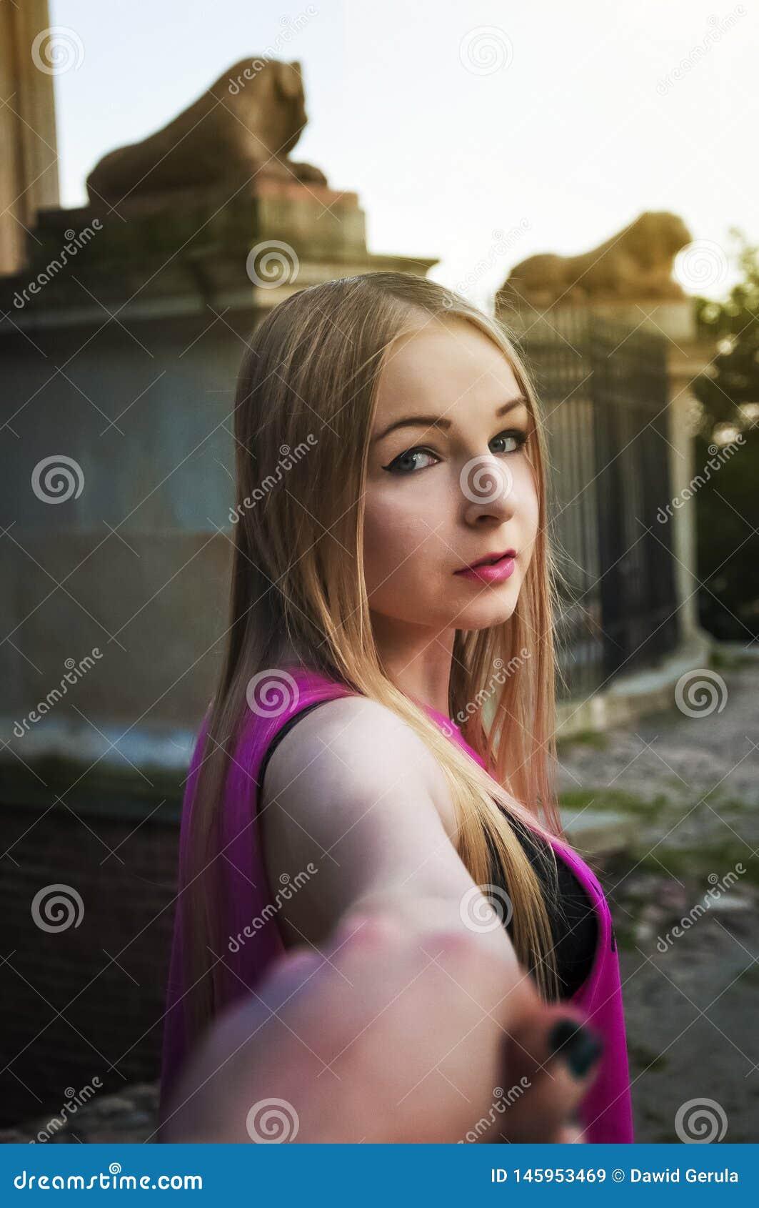 握跟随她的她的男朋友的手的年轻女人垂直的照片