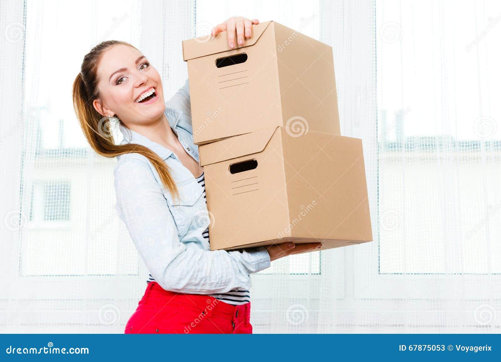 搬入房子运载的箱子的愉快的妇女