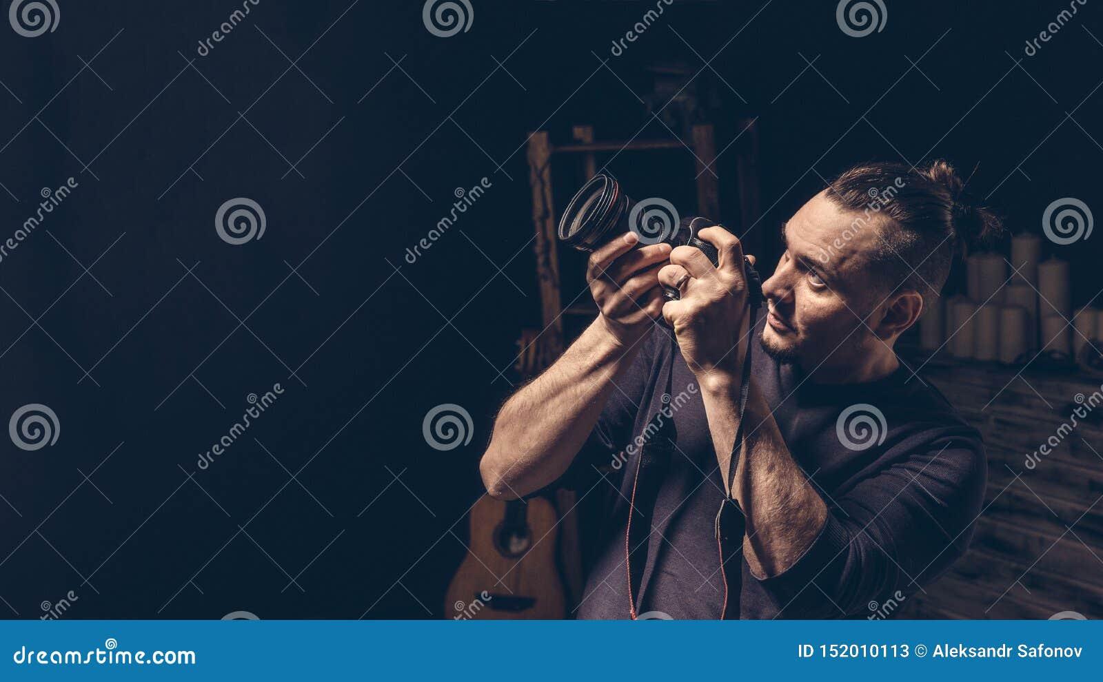 摄影师在他的瞄准观看的手上拿着照相机