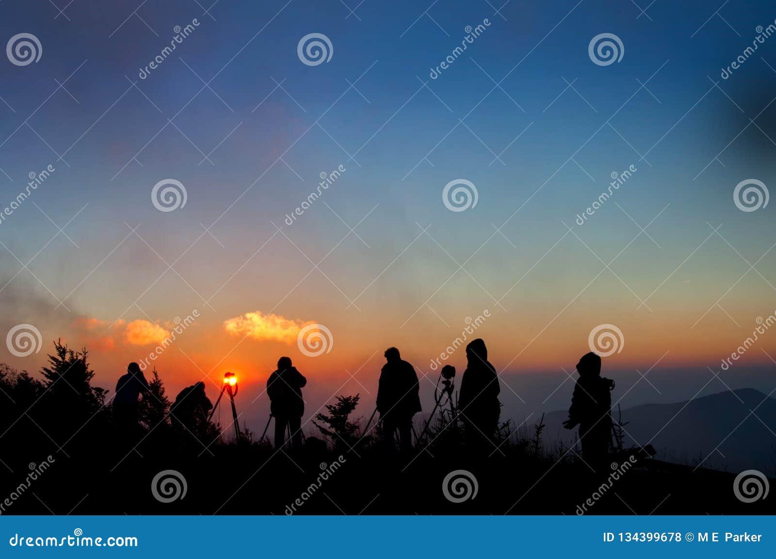 摄影师现出轮廓反对在北卡罗来纳山的有薄雾的日落