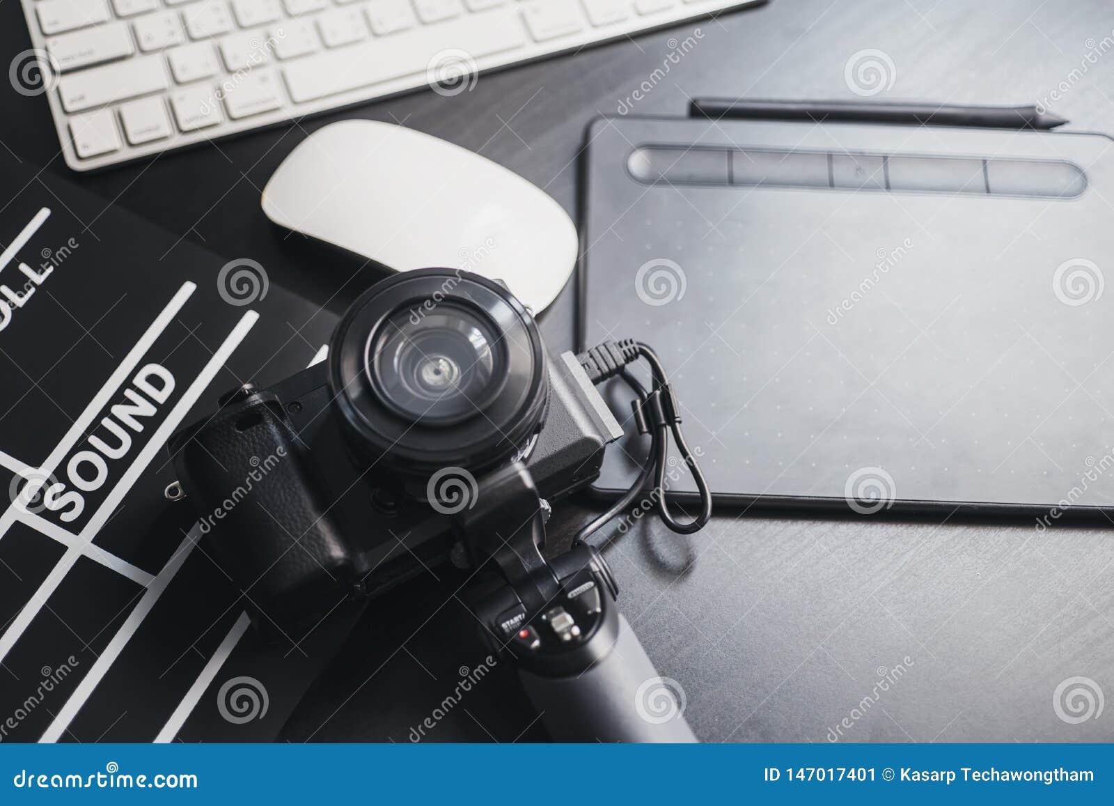 摄影师的专业摄影设备 与透镜、计算机和板岩影片,在木的数字笔的Mirrorless照相机