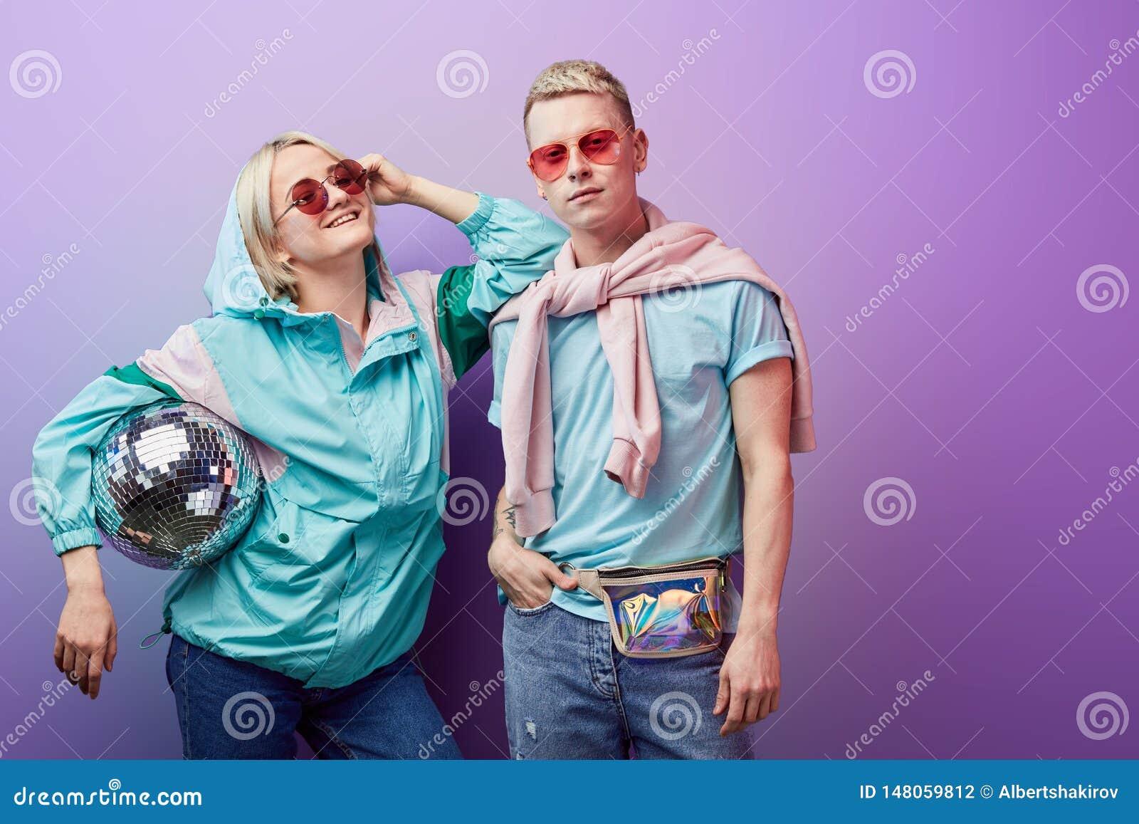 摆在与在紫罗兰色背景的迪斯科球的舞蹈家年轻时兴的夫妇