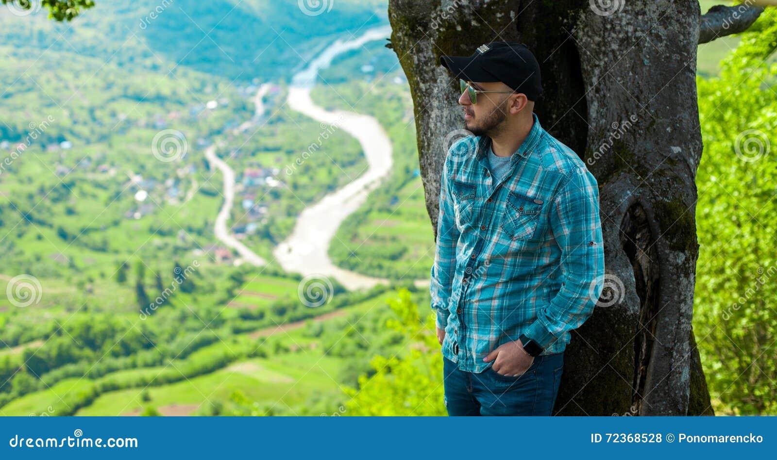摆在与山的太阳镜的人从后面环境美化