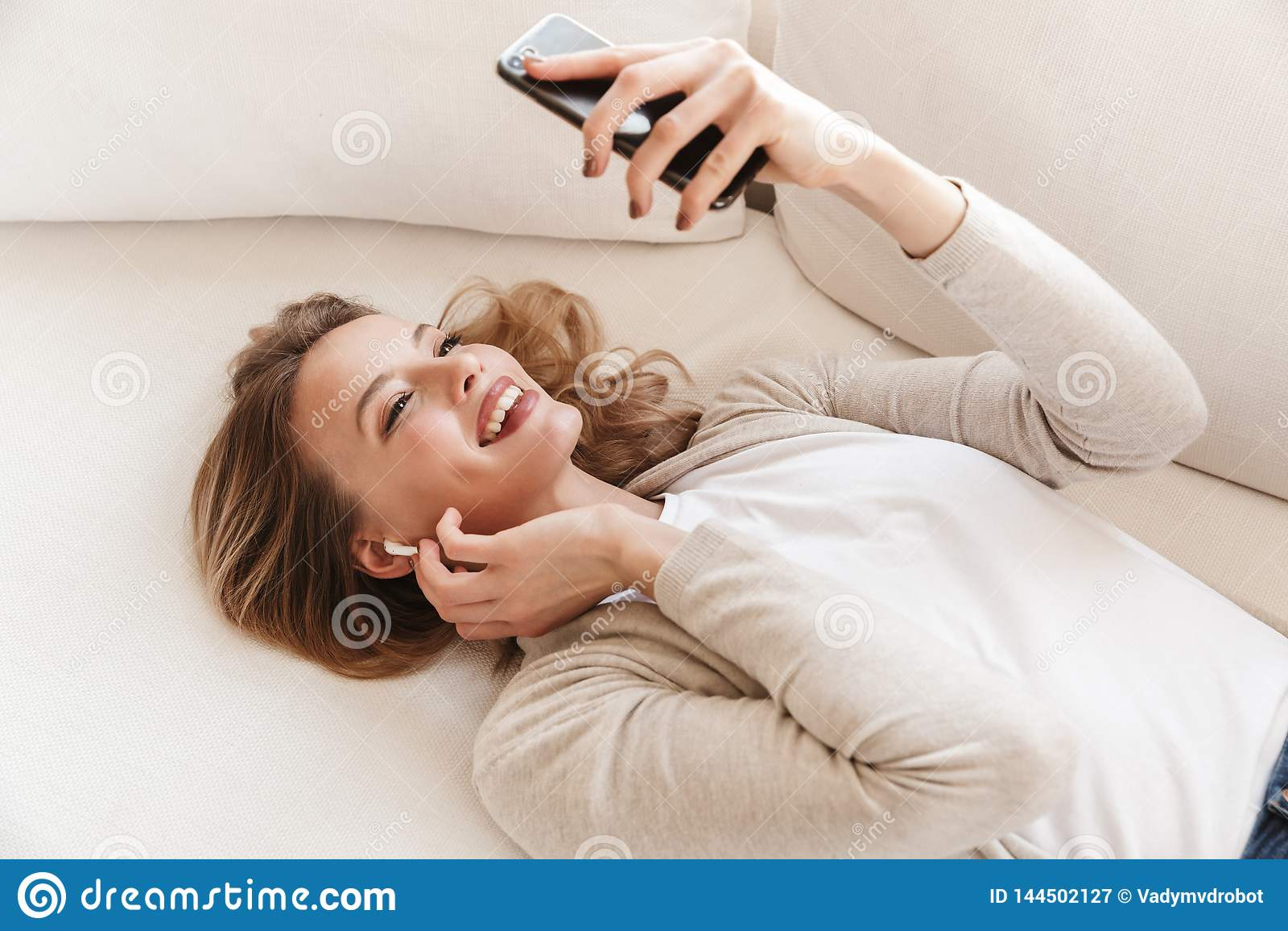 摆在与耳机的俏丽的白肤金发的妇女开会户内在家听的音乐