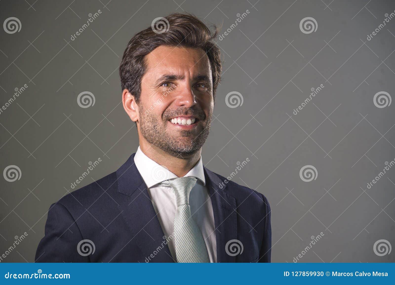 摆在为公司公司业务画象的衣服的英俊的愉快的人放松了和确信微笑的愉快隔绝在灰色