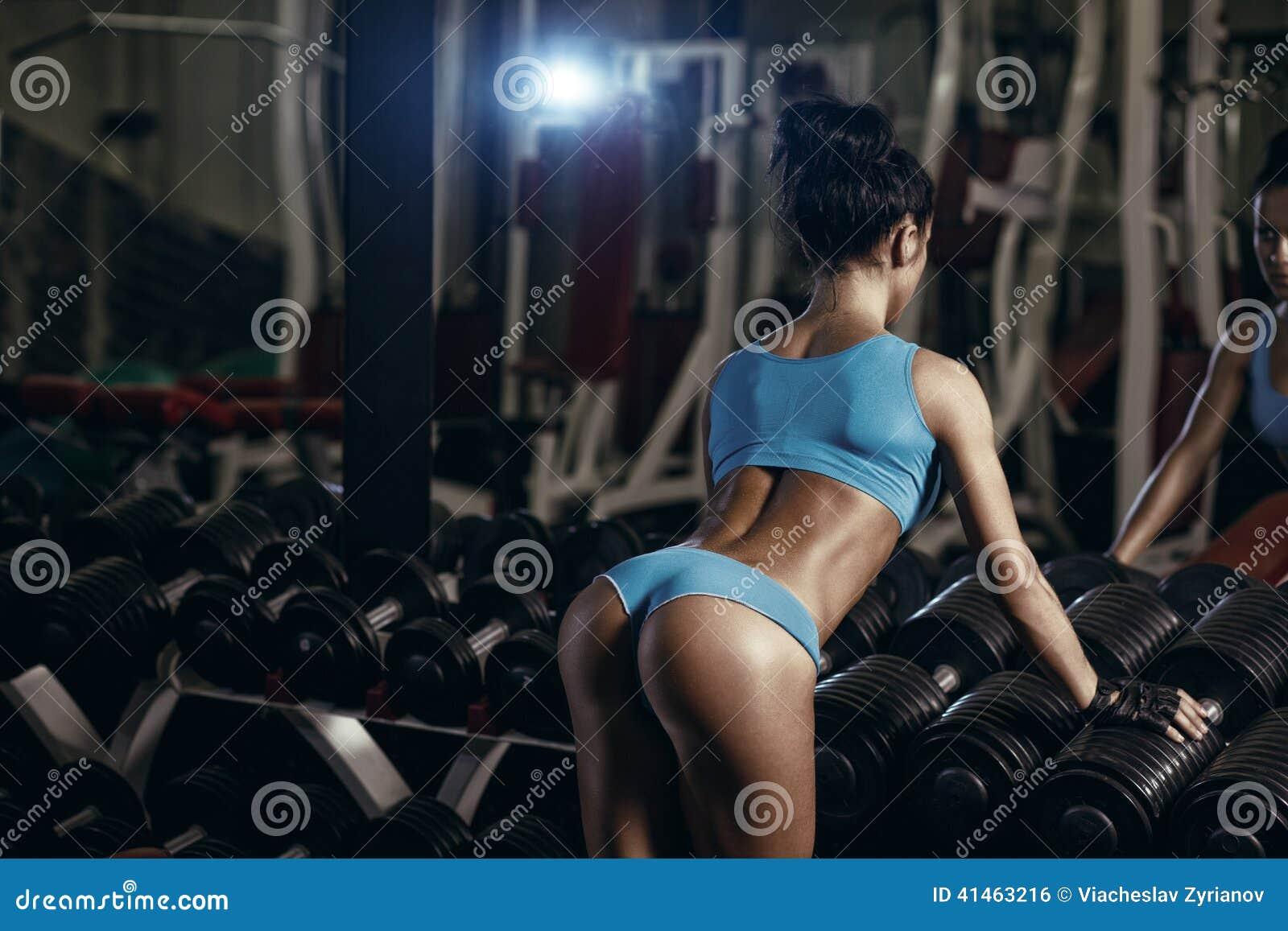 摆在健身房的后面观点的深色的性感的健身女孩