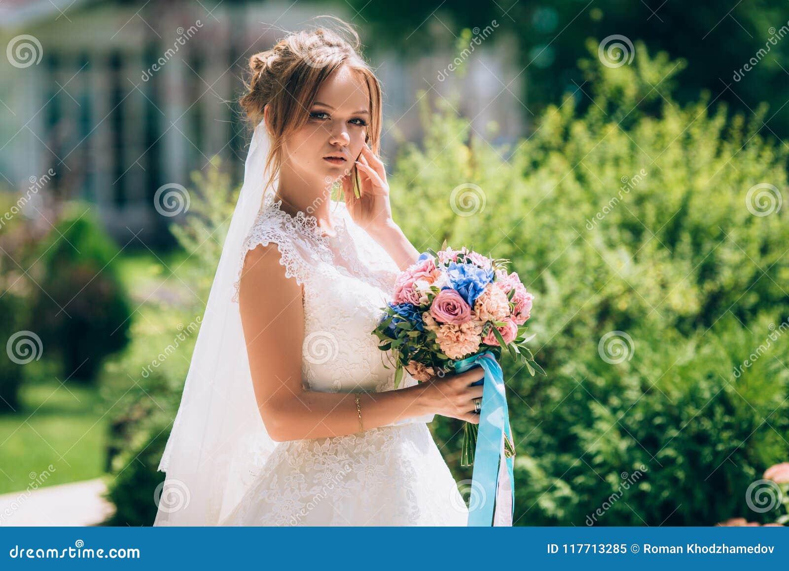 摆在反对绿叶的美丽的苗条新娘在公园 她在一套美丽的白色婚礼礼服打扮,