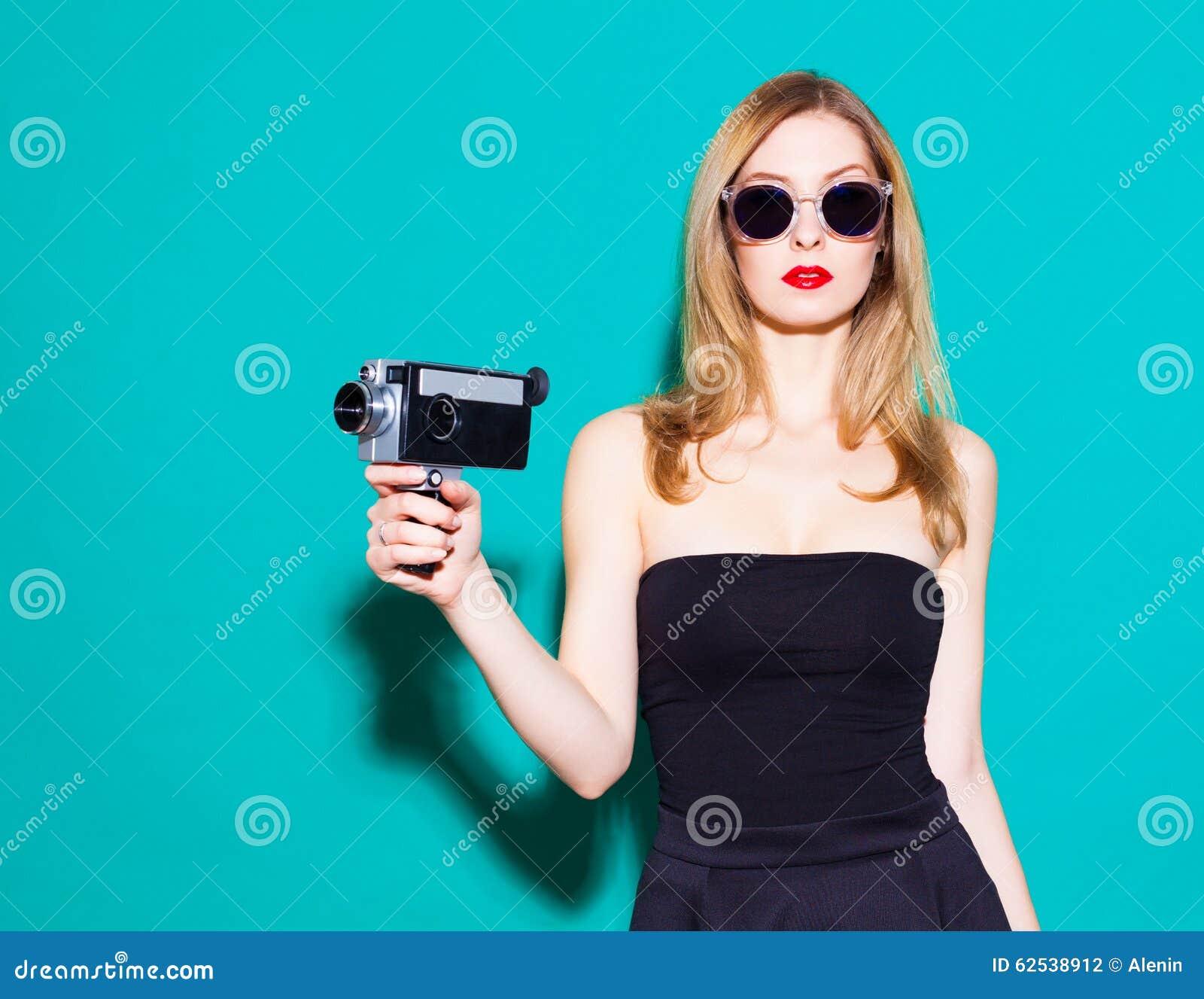 摆在和拿着在黑礼服和太阳镜的美丽的时兴的女孩葡萄酒电影摄影机在的绿色背景