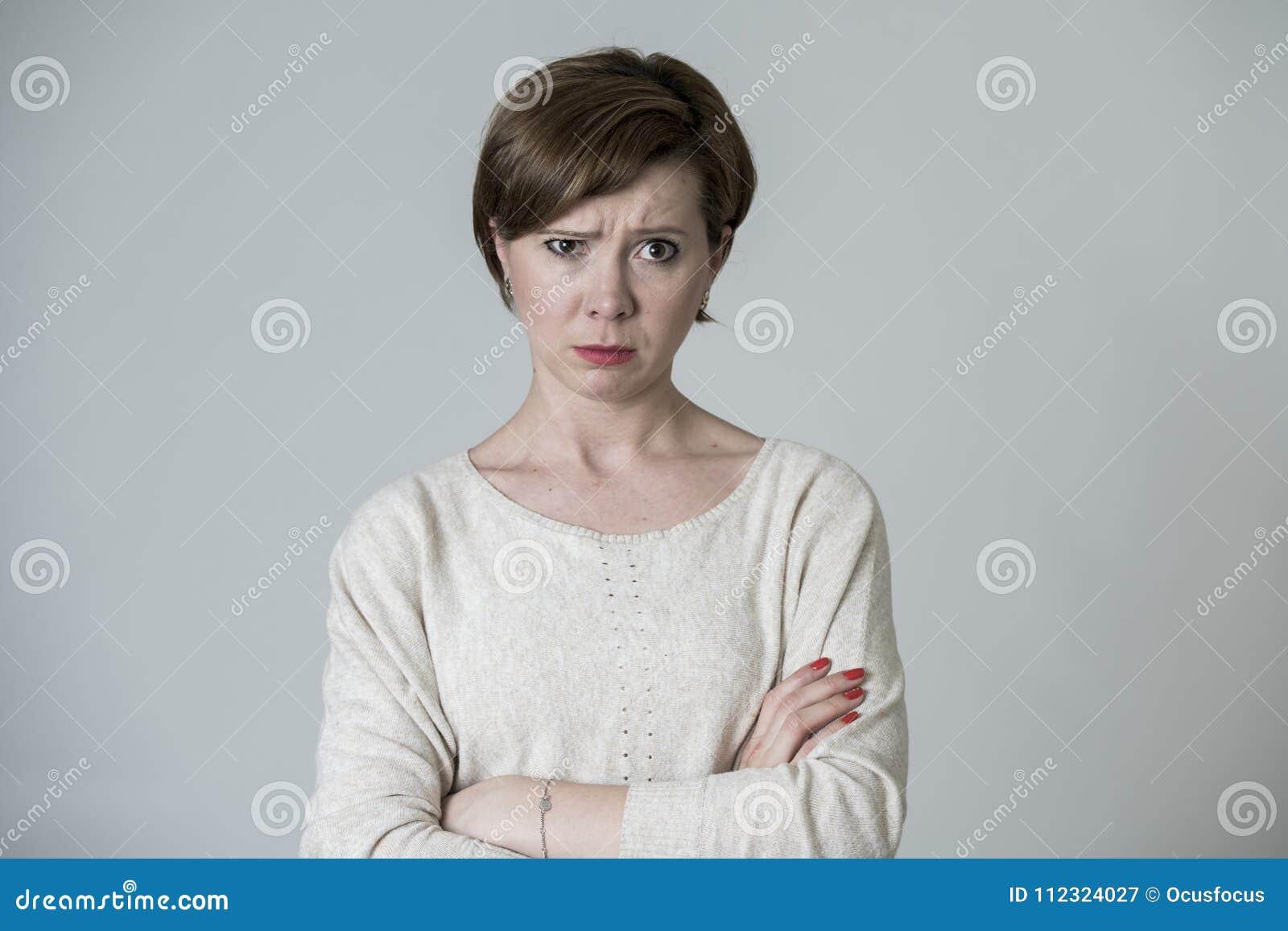 摆在哀伤和喜怒无常看的年轻疯狂的恼怒和生气红色头发妇女在表情的灰色背景隔绝的照相机