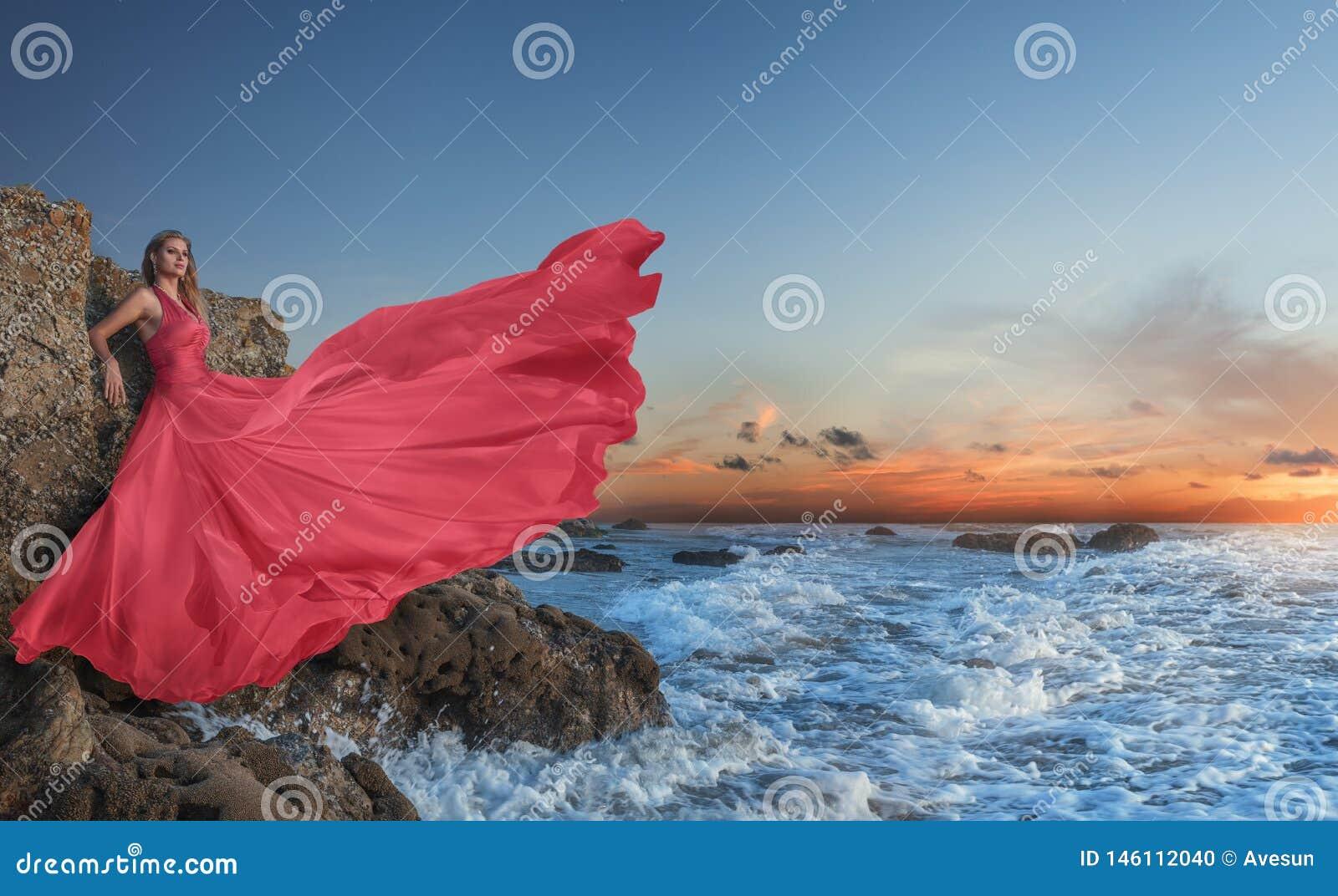 摆在在海滩的豪华长的礼服的美丽的年轻女人