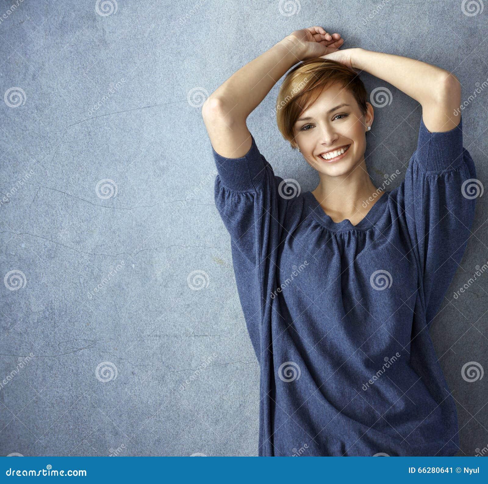 摆在墙壁的蓝色牛仔裤的愉快的少妇