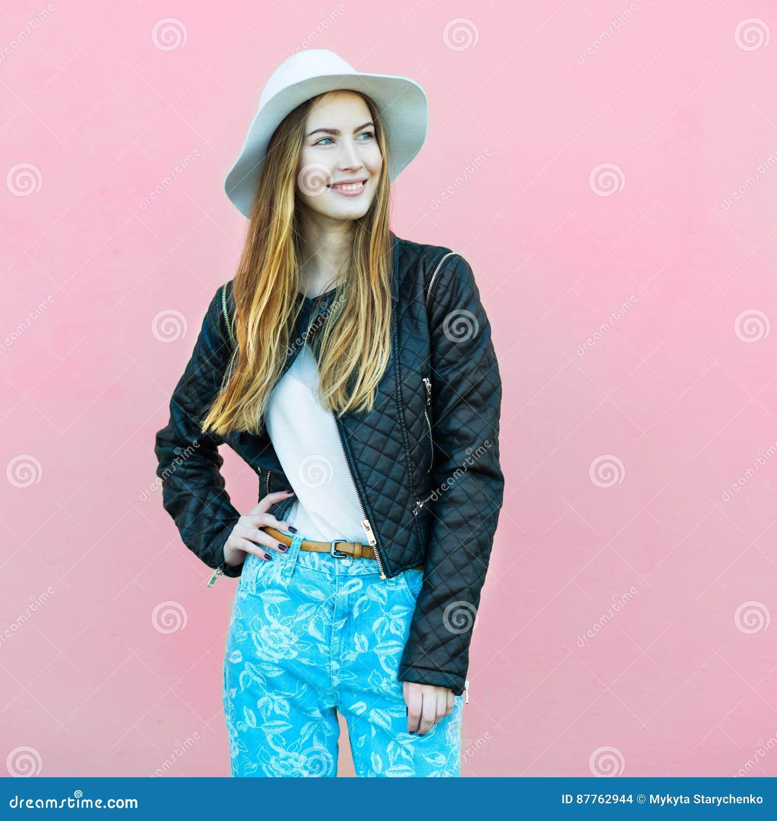 摆在墙壁附近的年轻愉快的时尚博客作者女孩穿偶然街道样式服装