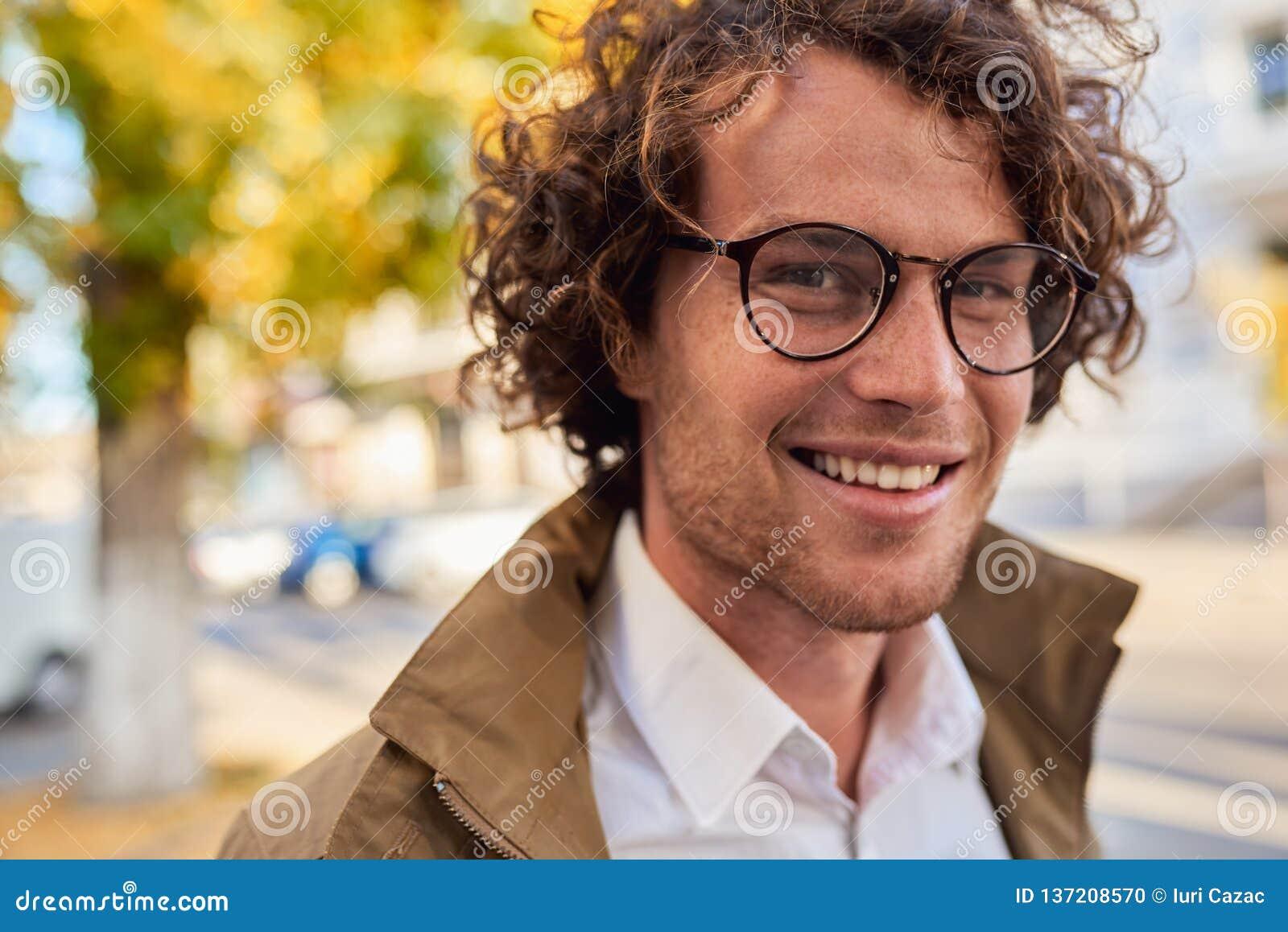 摆在年轻愉快的商人特写镜头水平的画象戴眼镜的微笑和户外 秋天街道的男生