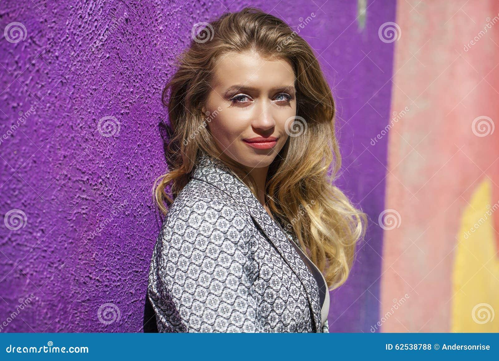 摆在户外在su的米黄短的礼服的年轻美丽的妇女