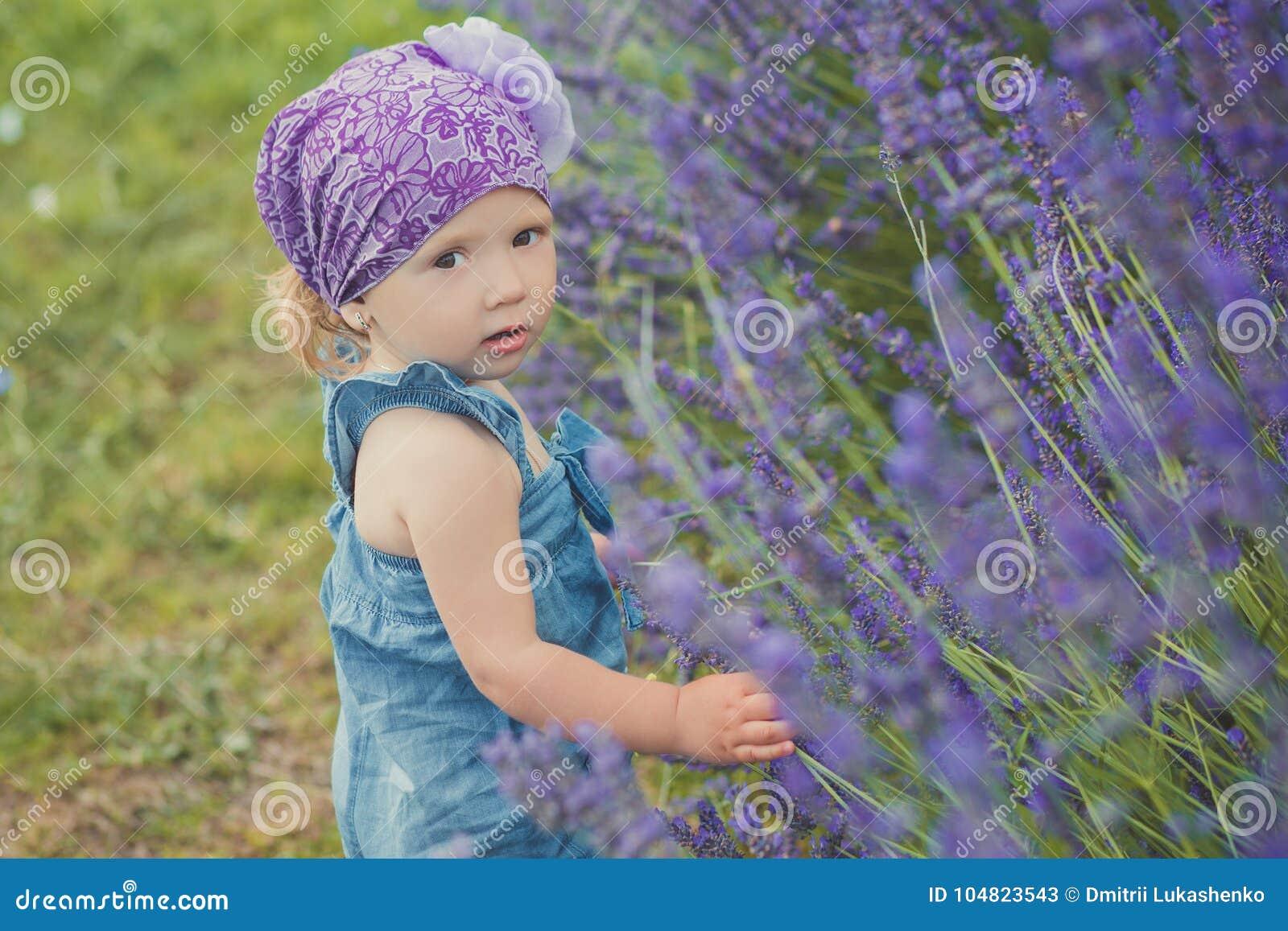 摆在接近lavander灌木佩带的牛仔裤的中央公园草甸的年轻秀丽儿童女孩穿戴和与我的紫罗兰色紫色班丹纳花绸