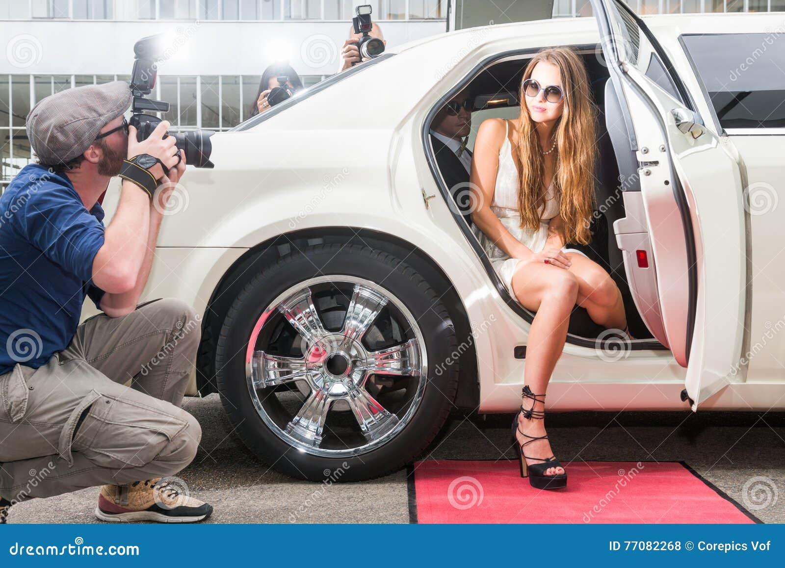 摆在无固定职业的摄影师的大型高级轿车的幼小母名人红色的