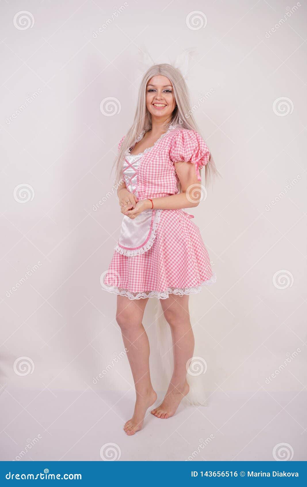 摆在有毛皮猫耳朵和一条长的蓬松尾巴的一件迷人的格子花呢披肩巴法力亚礼服的逗人喜爱的白肤金发的女孩在S的白色背景